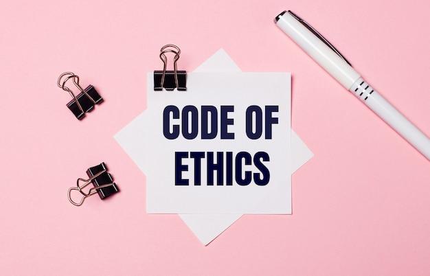 Sobre fundo rosa claro, clipes pretos, caneta branca e papel branco com o texto código de ética. postura plana