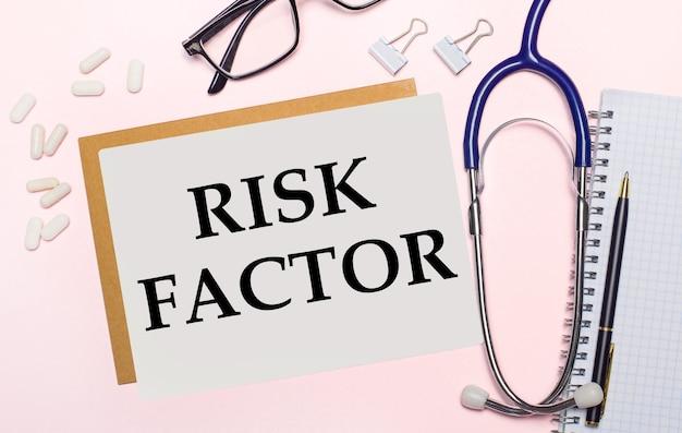 Sobre fundo rosa claro, estetoscópio, pílulas brancas e clipes para papel, óculos com armação preta e uma folha de papel com o texto fator de risco.