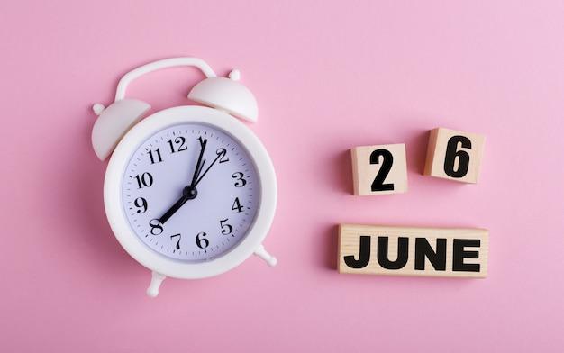 Sobre fundo rosa, despertador branco e cubos de madeira com data de 26 de junho