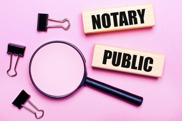 Sobre fundo rosa, lupa, clipes pretos e blocos de madeira com a inscrição tabelião público. conceito de negócios