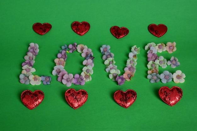 Sobre fundo verde, a palavra love é ladeada por flores multicoloridas em letras grandes. os corações estão alinhados acima e abaixo em uma linha