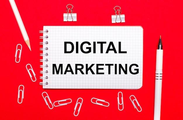Sobre fundo vermelho, caneta branca, clipes de papel branco, lápis branco e caderno com a inscrição marketing digital