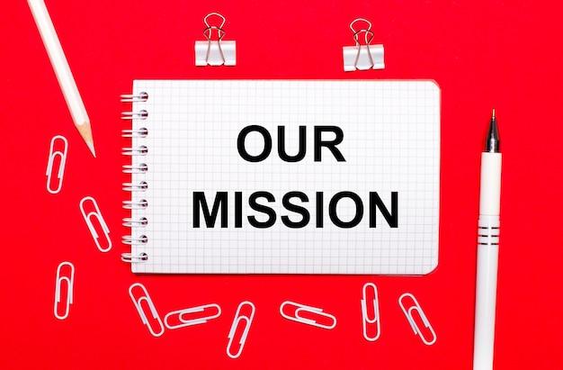 Sobre fundo vermelho, caneta branca, clipes de papel branco, lápis branco e caderno com o texto nossa missão