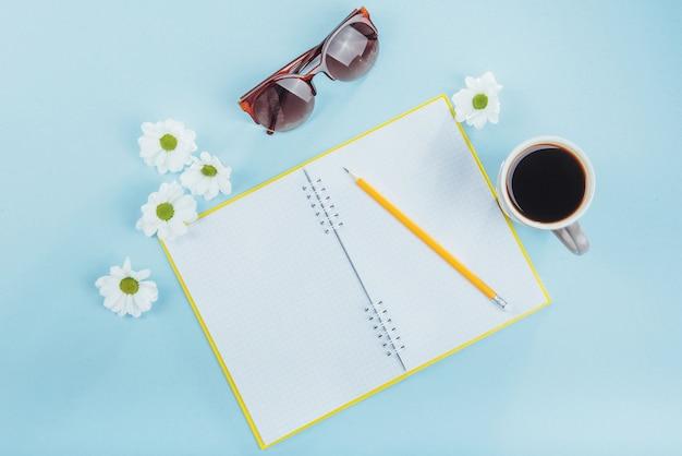 Sobre o caderno azul lápis, régua e flores brancas