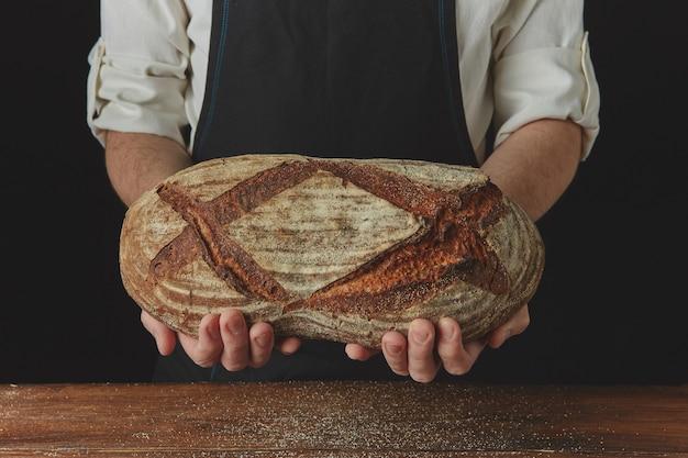 Sobre o fundo preto de uma mesa de madeira, as mãos do padeiro seguram pão oval orgânico fresco