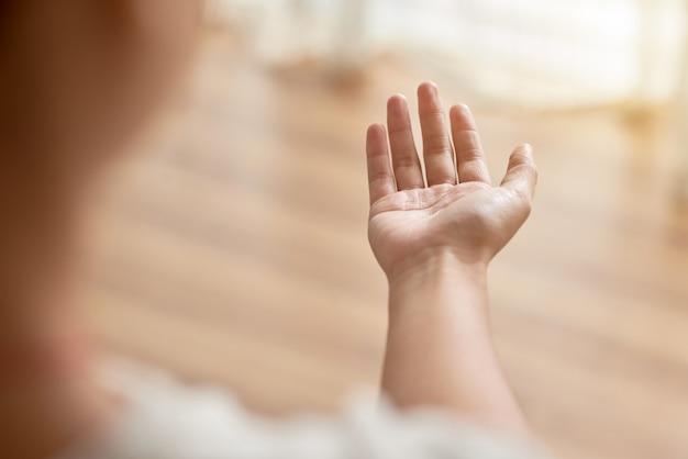 Sobre o ombro da mão da pessoa irreconhecível, esticada para a frente, implorando por ajuda