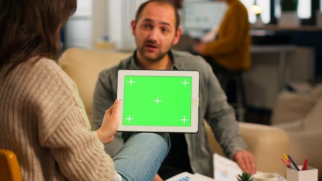 Sobre o ombro da mulher gerente sentada no sofá falando com um colega de trabalho segurando o tablet com tela verde, enquanto a equipe diversificada trabalha. projeto de planejamento de pessoas multiétnicas no display chroma key