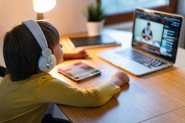 Sobre o ombro de uma criança fazendo cursos virtuais
