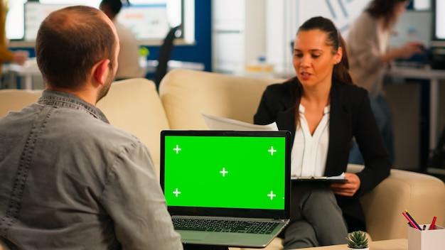 Sobre o ombro do gerente sentado no sofá falando com o colega segurando o laptop com tela verde enquanto diversificada equipe trabalhando no fundo. projeto de planejamento de pessoas multiétnicas no display chroma key