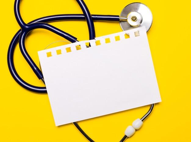 Sobre um fundo amarelo brilhante, um estetoscópio azul e uma folha de papel com um local para inserir texto. conceito médico