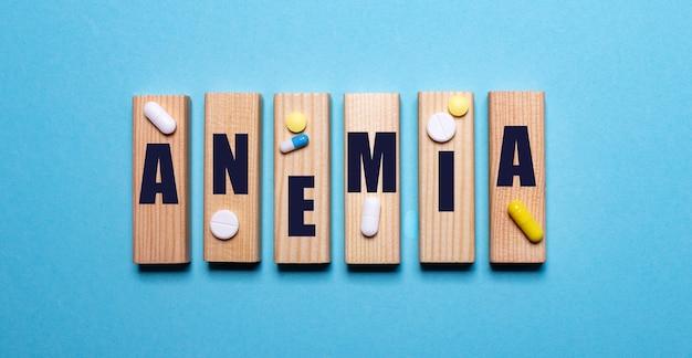 Sobre um fundo azul, blocos de madeira com a palavra anemia e comprimidos. conceito médico