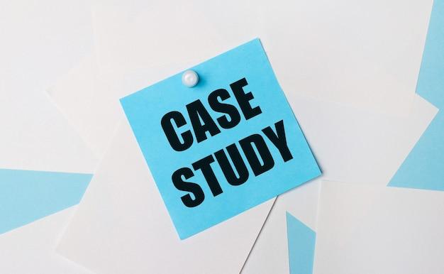 Sobre um fundo azul claro, folhas de papel quadradas brancas. um adesivo quadrado azul claro com o texto estudo de caso é colado a eles usando um clipe de papel branco.