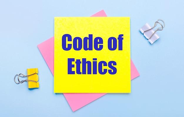 Sobre um fundo azul claro, há clipes de papel amarelos e brancos, notas adesivas rosa e amarelas com o texto código de ética