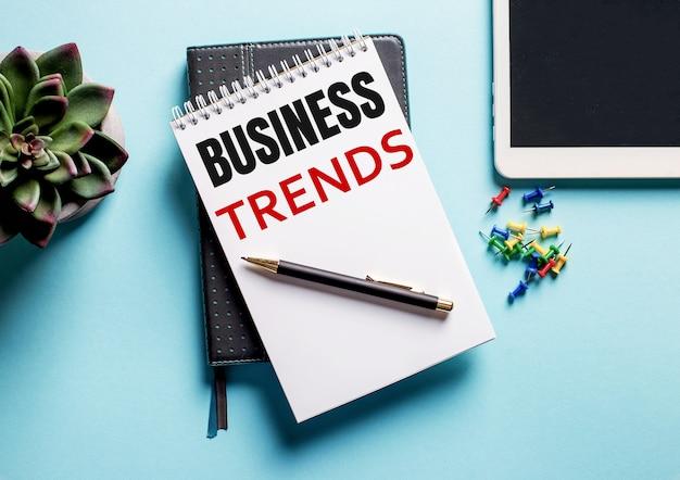 Sobre um fundo azul claro, há um vaso de planta, um tablet e um semanário com o texto tendências de negócios