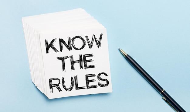 Sobre um fundo azul claro, há uma caneta preta e uma pilha de papel branco com o texto conheça as regras