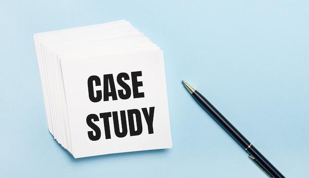 Sobre um fundo azul claro, há uma caneta preta e uma pilha de papel branco com o texto estudo de caso