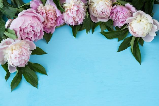 Sobre um fundo azul claro, peônias rosa brancas formam um quadro