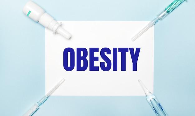 Sobre um fundo azul claro, seringas, um frasco de remédio, uma ampola e uma folha de papel branca com o texto obesidade. conceito médico.