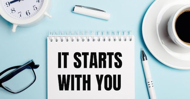 Sobre um fundo azul claro, uma xícara branca com café, um despertador branco, uma caneta branca e um caderno com a inscrição começa com você. vista de cima