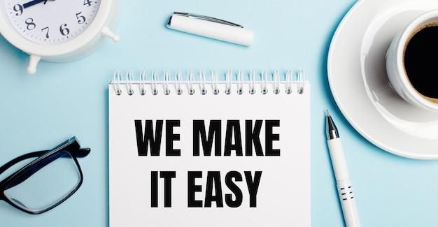 Sobre um fundo azul claro, uma xícara branca com café, um despertador branco, uma caneta branca e um caderno com a inscrição ficamos fácil. vista de cima