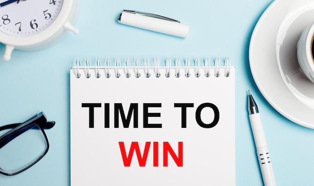 Sobre um fundo azul claro, uma xícara branca com café, um despertador branco, uma caneta branca e um caderno com a inscrição hora de ganhar. vista de cima