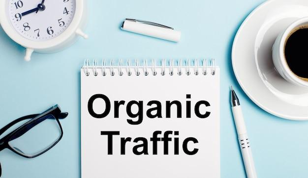 Sobre um fundo azul claro, uma xícara branca com café, um despertador branco, uma caneta branca e um caderno com a inscrição tráfego orgânico. vista de cima