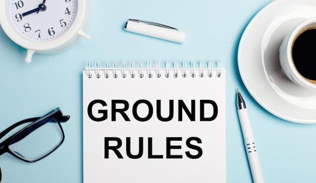 Sobre um fundo azul claro, uma xícara branca com café, um despertador branco, uma caneta branca e um caderno com o texto regras fundamentais