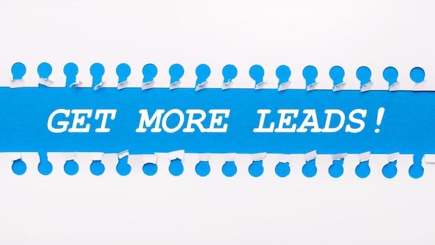 Sobre um fundo azul com o texto get more leads duas tiras de papel brancas rasgadas.