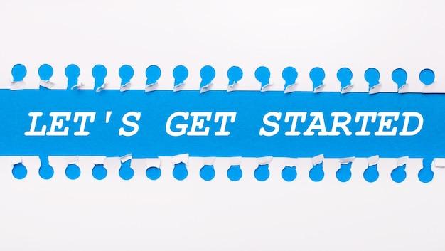Sobre um fundo azul com o texto vamos começar duas tiras de papel brancas rasgadas.