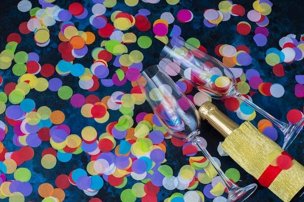 Sobre um fundo azul duas taças de champanhe, uma garrafa de champanhe e confete brilhante