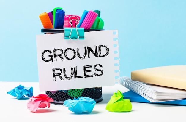 Sobre um fundo azul - um suporte com marcadores brilhantes, blocos de notas e pedaços de papel amassado multicoloridos. uma folha de papel com o texto regras fundamentais.