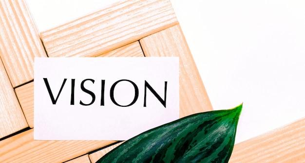Sobre um fundo branco, blocos de madeira, um cartão branco com o texto visão e uma folha verde da planta. vista de cima