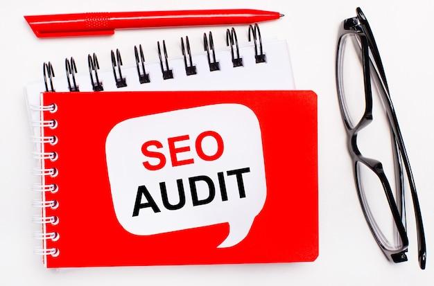 Sobre um fundo branco, blocos de notas branco e vermelho, óculos pretos, uma caneta vermelha e um cartão branco com o texto seo audit.