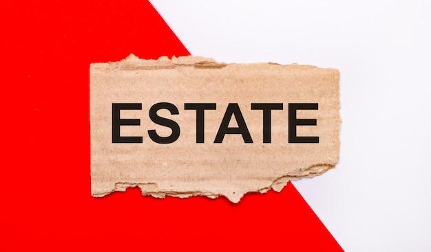 Sobre um fundo branco e vermelho, papelão marrom rasgado com o texto estate