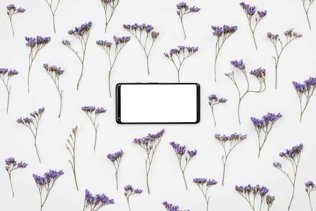 Sobre um fundo branco, há flores silvestres e um telefone com uma tela em branco. lugar para texto,
