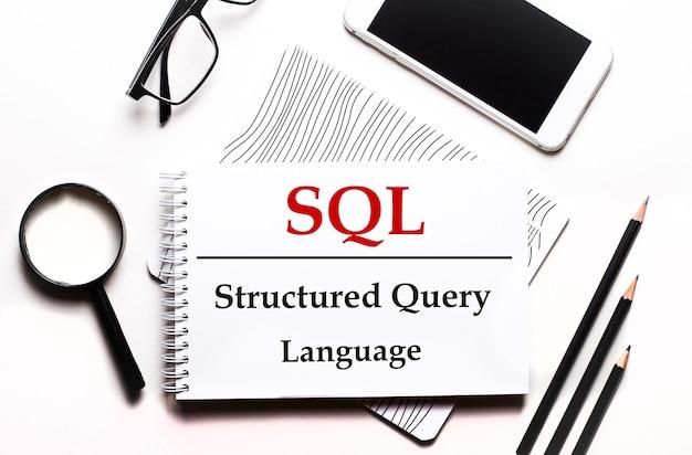 Sobre um fundo branco óculos, lupa, lápis, smartphone e um notebook com o texto sql structured query language.