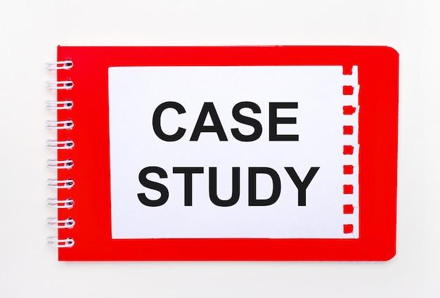 Sobre um fundo branco - um caderno vermelho brilhante em espiral. nele está uma folha de papel em branco com o texto estudo de caso