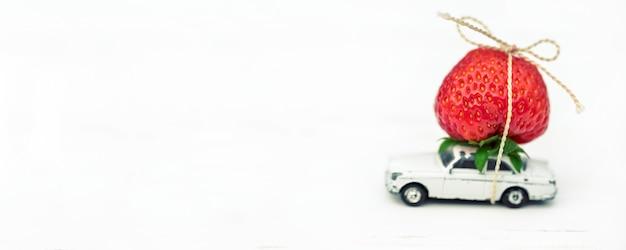 Sobre um fundo branco, um pequeno carro de brinquedo com inscrição de lugar de morangos vermelhos.