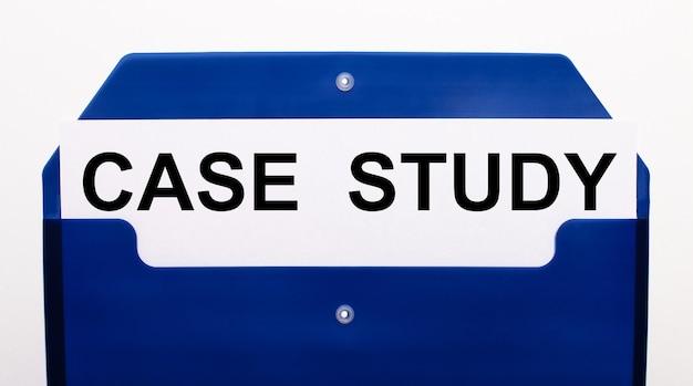 Sobre um fundo branco, uma pasta azul para papéis. na pasta está uma folha de papel com as palavras estudo de caso.