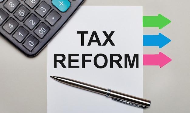 Sobre um fundo cinza claro, uma calculadora, uma folha branca com o texto tax reform, uma caneta e adesivos multicoloridos brilhantes. vista de cima
