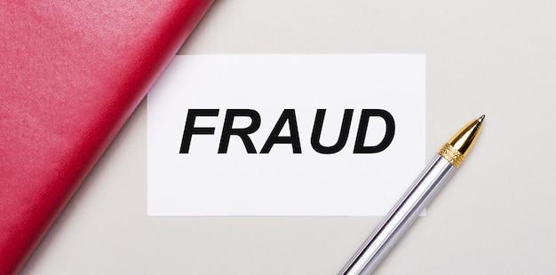Sobre um fundo cinza claro, uma caneta dourada, um caderno bordô e um cartão branco em branco com um local para inserir o texto fraude. conceito de negócios. modelo