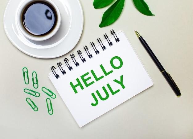 Sobre um fundo cinza claro, uma xícara de café branca, clipes de papel verdes e uma folha verde de uma planta, além de uma caneta e um caderno com as palavras olá julho.