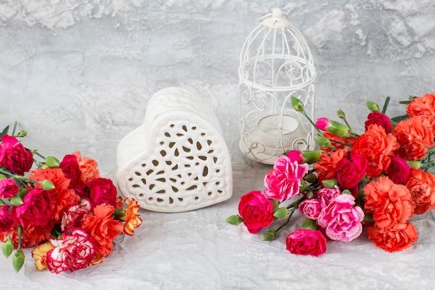 Sobre um fundo cinza, cravos brilhantes, um coração de rendilhado feito de cerâmica e uma gaiola decorativa branca