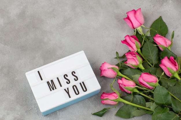Sobre um fundo cinza de concreto um buquê de rosas e a inscrição sinto sua falta