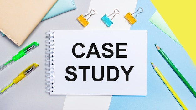 Sobre um fundo cinza e azul estão os papéis de carta verde-amarelo, um caderno com o texto estudo de caso. postura plana. modelo.