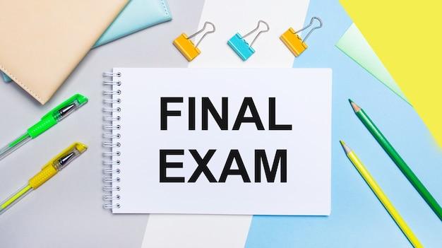 Sobre um fundo cinza e azul estão os papéis de carta verde-amarelo, um caderno com o texto exame final