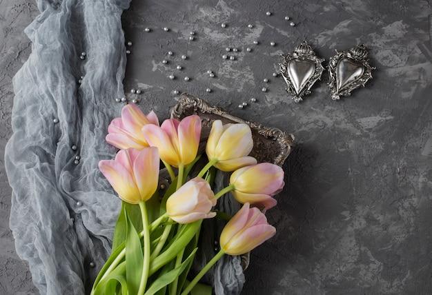 Sobre um fundo cinza em um prato rosa há tulipas cor de rosa, pérolas cinzentas e dois corações retrô