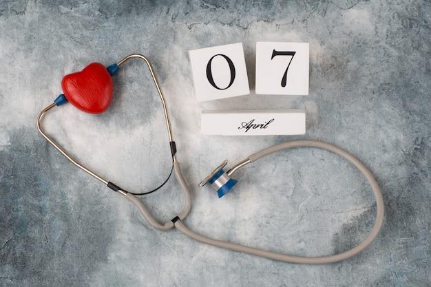 Sobre um fundo cinza um estetoscópio e um coração vermelho e uma data do calendário de 7 de abril
