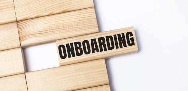 Sobre um fundo claro, blocos de madeira com o texto onboarding. vista superior em close-up.