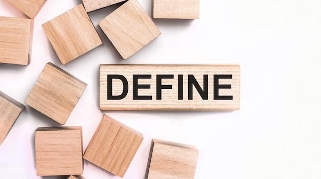 Sobre um fundo claro, cubos de madeira e um bloco de madeira com o texto define